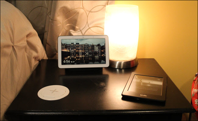 A nightstand with a wireless charger set into the surface, a kindle, and Google Home Hub