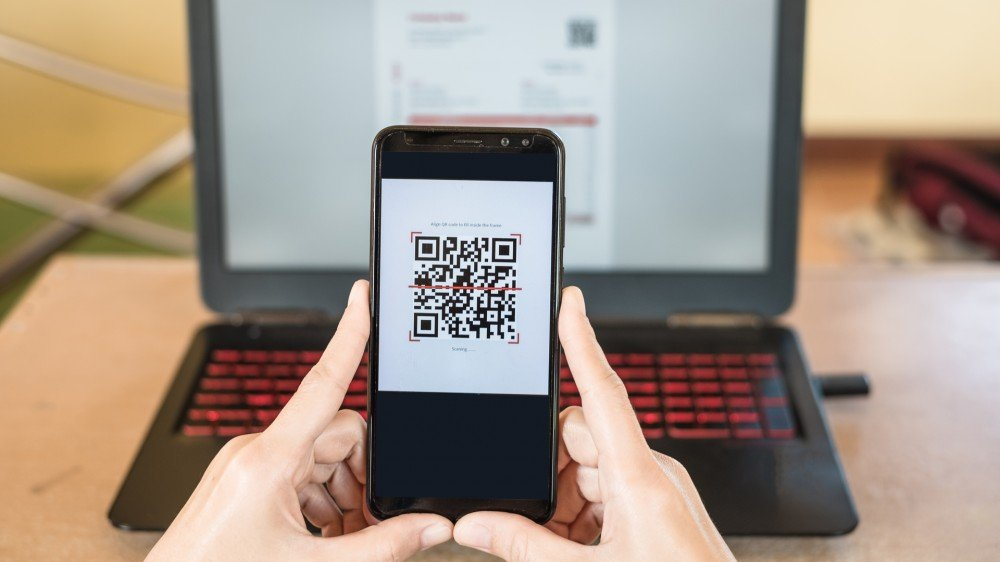 Close up of hand holding smartphone with a QR code on it, in front of a laptop